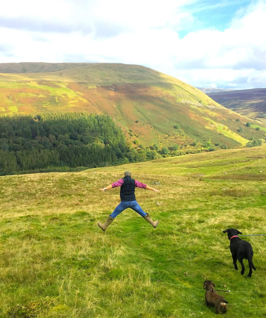 Man jumping in the air on a dog walk in the Yorkshire Dales